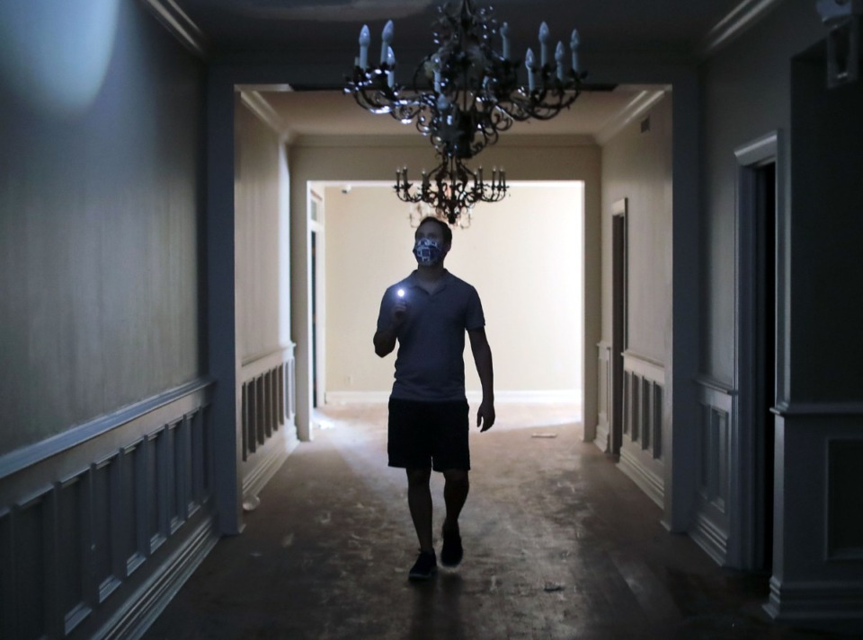 <strong>Matt Uselton uses a flashlight to navigate the dark hallways of the Racquet Club on Aug. 14, 2020.</strong> (Patrick Lantrip/Daily Memphian)