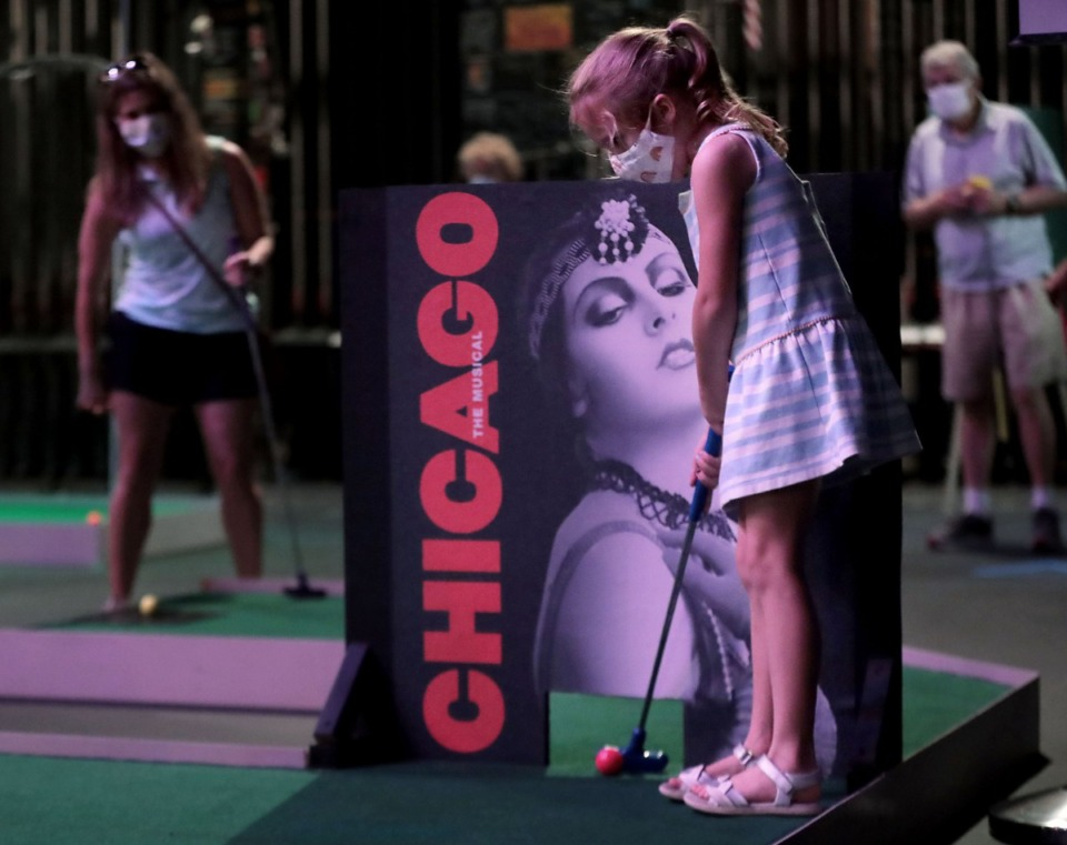 <strong>Young Ella Allen takes a putt in front of a Chicago-themed obstacle while her mom Kim looks on in the background at the Orpheum Theatre in Memphis Aug. 15, 2020. With shows and concerts on hold due to the COVID-19 pandemic, the Orpheum set up a 9-hole Broadway inspired mini golf course on the stage.</strong> (Patrick Lantrip/Daily Memphian)