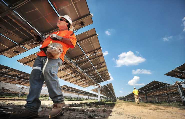 <strong>Electrician Michael Haines wires up a bank of solar panels at the new 421 acre solar farm under construction east of Millington on Sept. 18, 2018.</strong>  (Jim Weber/Daily Memphian)