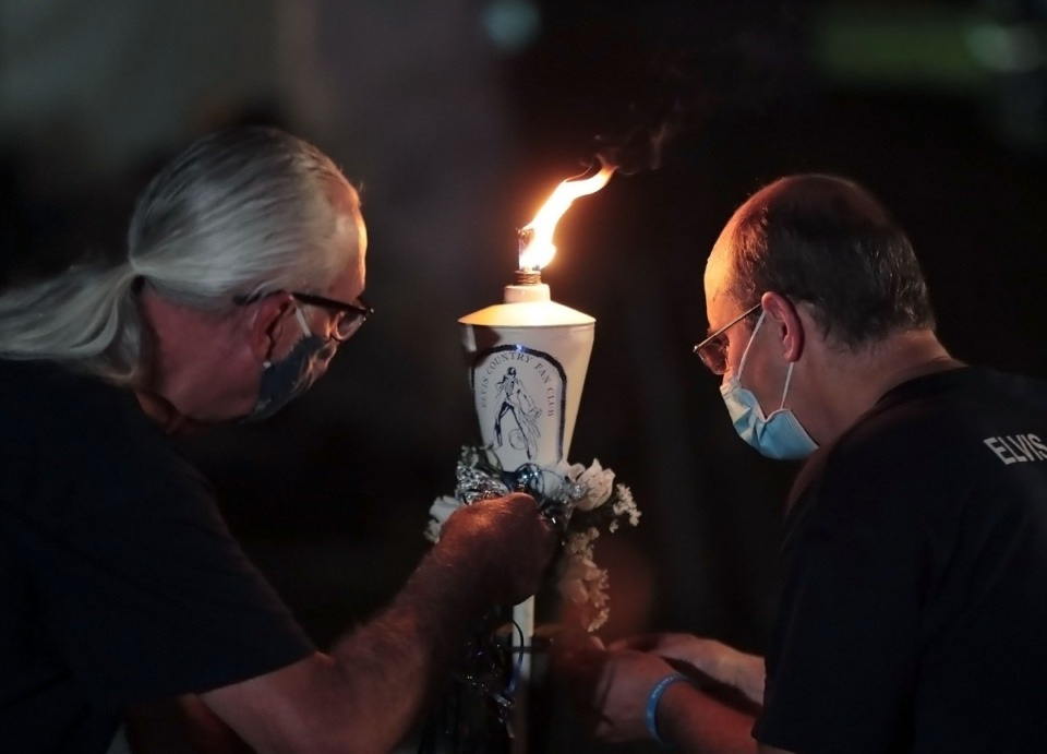 <strong>Two Graceland employees light a flame for the candlelight vigil Saturday, Aug. 15, 2020. The number of people allowed to attend in person was limited due to social distancing, but more than 7 million viewers watched online. </strong>(Patrick Lantrip/Daily Memphian)