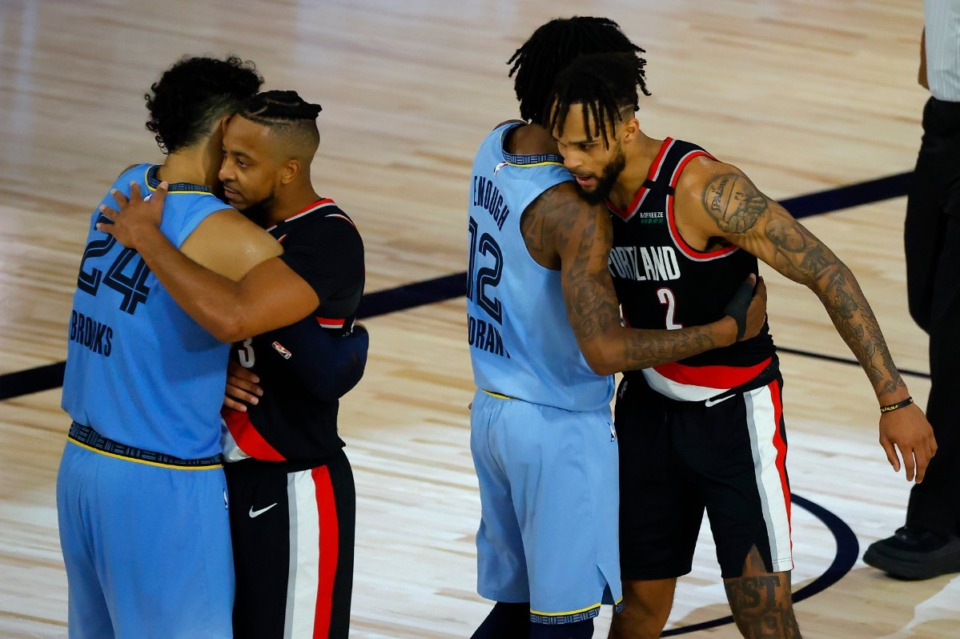 <strong>Portland Trail Blazers' Gary Trent Jr. (2) hugs Memphis Grizzlies' Ja Morant (12) while Portland Trail Blazers' CJ McCollum hugs Memphis Grizzlies' Dillon Brooks (24) Saturday after their game.</strong> (Kevin C. Cox/Pool Photo via AP)