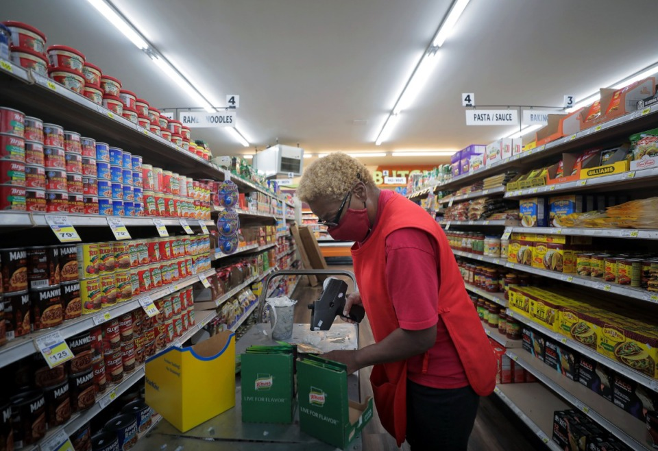<strong>Vickie Byrd stocks the shelves of the now re-opened High Point Grocery on Aug. 14, 2020.</strong> (Patrick Lantrip/Daily Memphian)