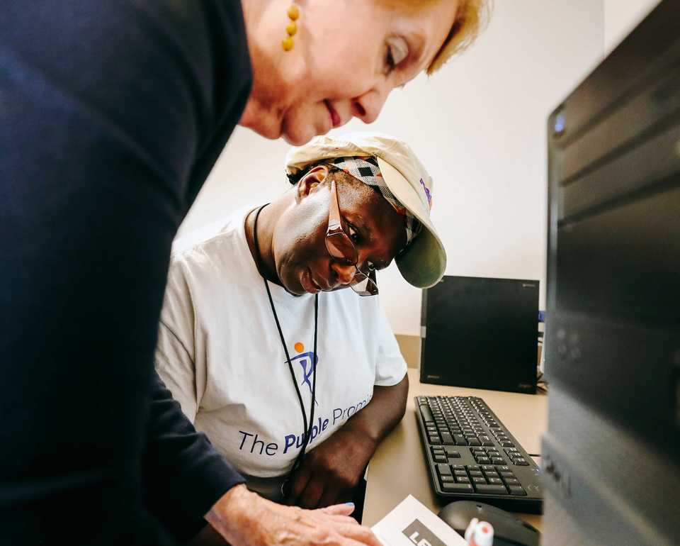 <strong>Esther Jackson (bottom), a material handler at FedEx, works with LiFE coach Mary Brignole to enroll in the Learning inspired by FedEX (LiFE) program. The partnership program between FedEx and the University of Memphis aims to offer Memphis hub employees an opportunity to earn a tuition-free degree.</strong> (Houston Cofield/Daily Memphian)