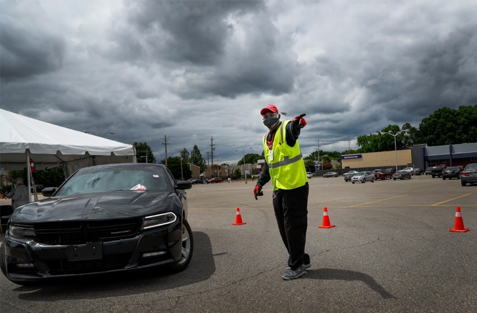 <strong>Christ Community Health Center employee Jessie Tate directs traffic as hundreds of Memphians line up for COVID-19 testing in Hickory Hill on Tuesday, May 19, 2020</strong>. (Mark Weber/Daily Memphian)