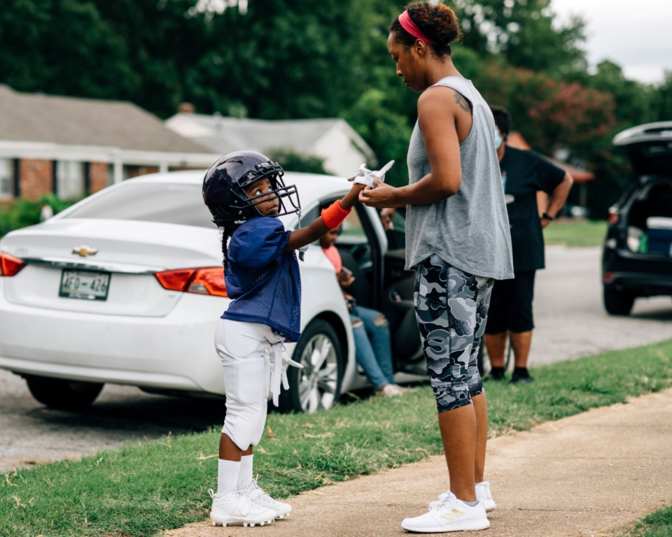 <strong>Janel Bear (right) puts a glove on her daughter Casey Beard before she heads out to practice. The Memphis Knights Youth Sports Association sponsors co-ed tackle and flag football teams for kids 5-13 and are preparing for the first game in early September.</strong> (Houston Cofield/Special to The Daily Memphian)