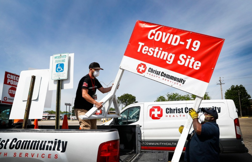 <strong>Christ Community Health Services staff members Blake Chastain (left) and Derico Miller (right) set up a drive-thru COVID-19 testing site on Friday, April 17, 2020 in the Mendenhall Square Shopping Center.</strong> (Mark Weber/Daily Memphian)
