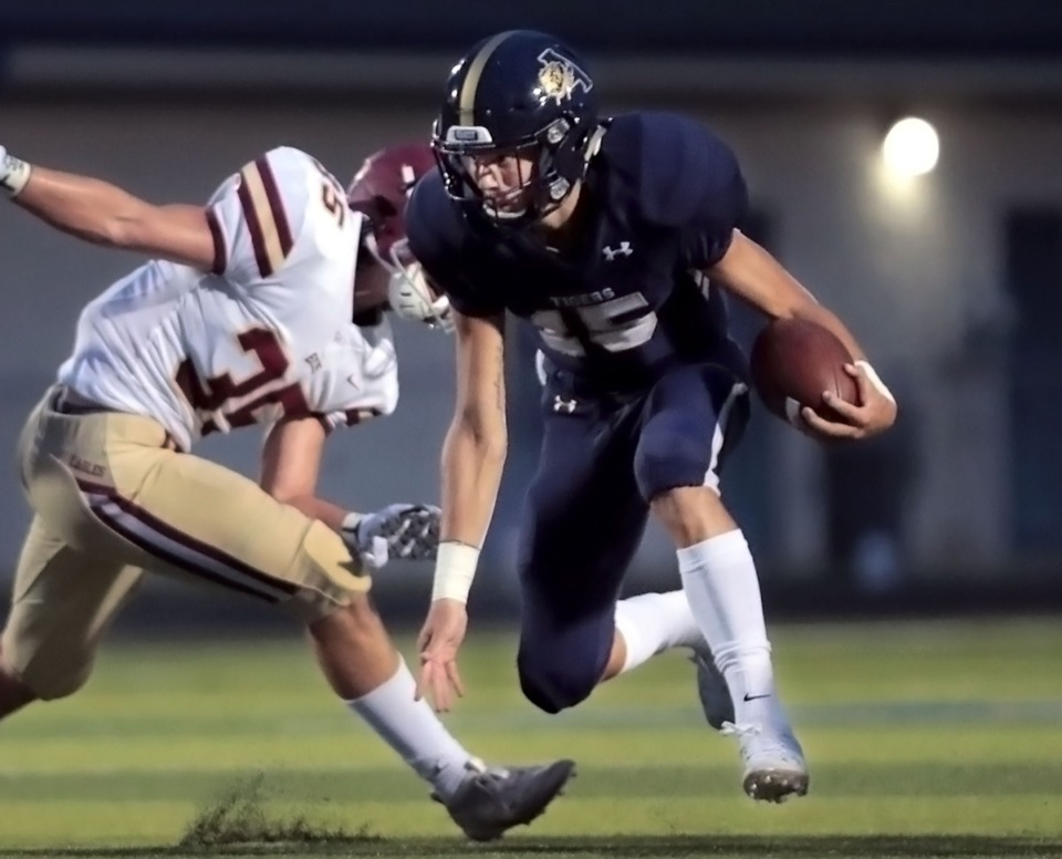 <strong>Arlington High School quarterback Zach Baker (15) evades a tackle during an Aug. 27, 2020, home game against Evangelical Christian School.</strong> (Patrick Lantrip/Daily Memphian)