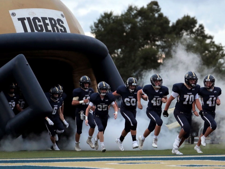 <strong>The Arlington Tigers take the field amid a cloud of smoke during an Aug. 27, 2020, home game against ECS.</strong> (Patrick Lantrip/Daily Memphian)