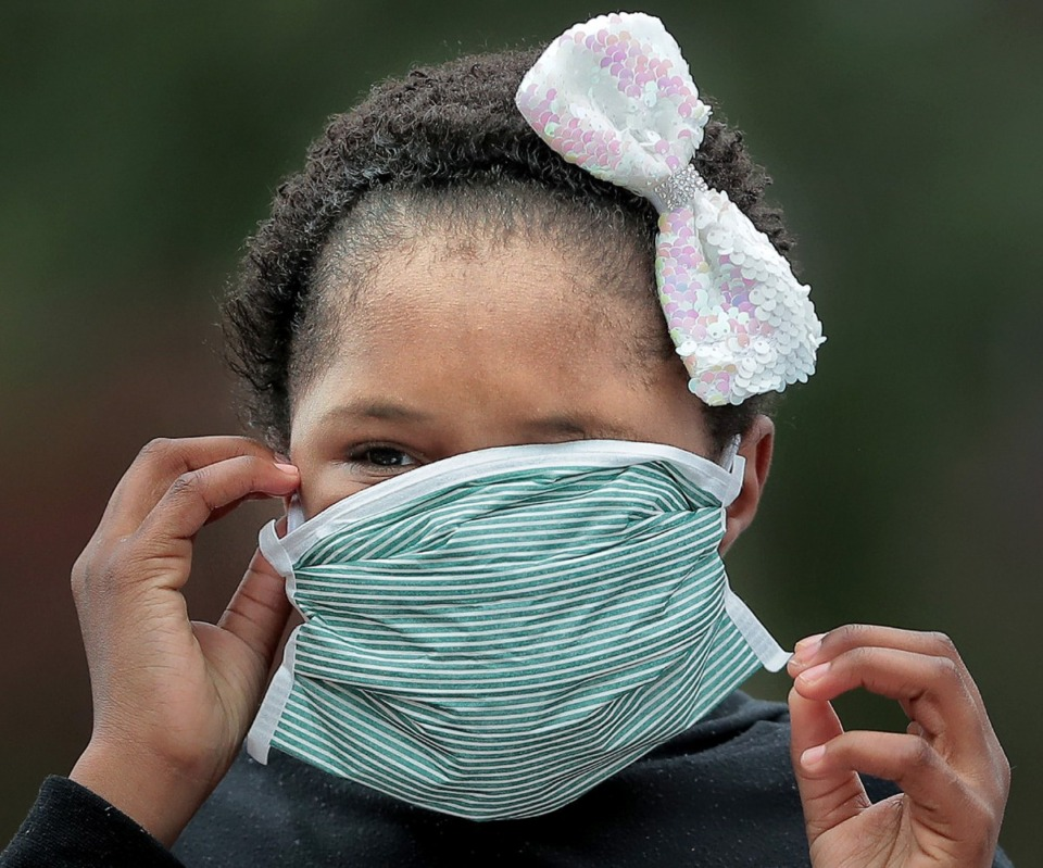 <strong>Erivana Sevion (in a file photo) struggled to get her mask to sit right during a food-basket giveaway earlier this year at Pursuit of God Church in Frayser.</strong> (Jim Weber/Daily Memphian)
