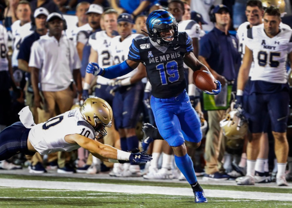 <strong>Memphis running back Kenneth Gainwell (right) scrambles past Navy defender Vincent Thomas Jr. (left) on his way to a 75 yard touchdown during action in their college football game at the Liberty Bowl Memorial Stadium Thursday, Sept. 26, 2019.</strong> (Mark Weber/Daily Memphian file)