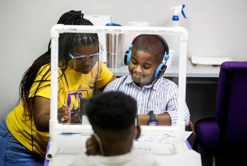 <strong>New Life Learning Academy Director Kelli Willis (left) works with Mason Dunning, 7, a second grader at White Station Elementary on his classwork on Monday, Aug. 31, 2020.</strong> (Mark Weber/Daily Memphian)