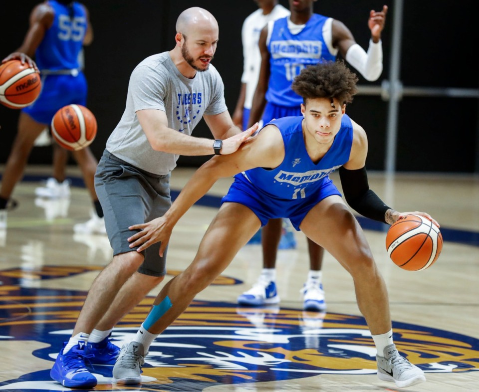 <strong>University of Memphis guard Lester Quinones (right) works on his dribbling skills with assistant coach Cody Toppert (left) during practice Aug. 6, 2019.</strong> (Mark Weber/Daily Memphian file).