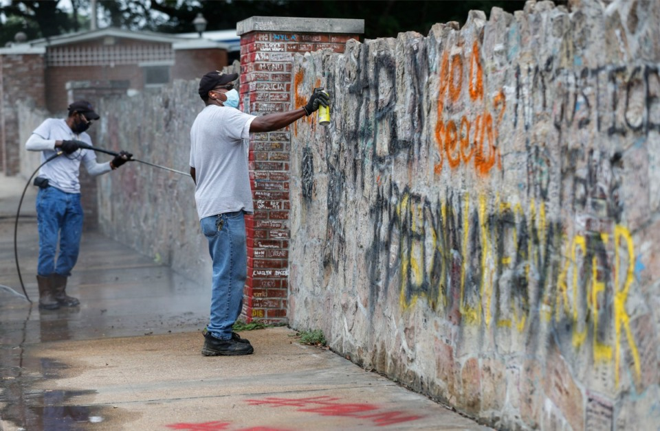 <strong>Graceland maintenance staff member Bobby Sample tries to remove BLM messages on the Graceland wall after protesters spray pained the wall overnight.</strong> (Mark Weber/The Daily Memphian)