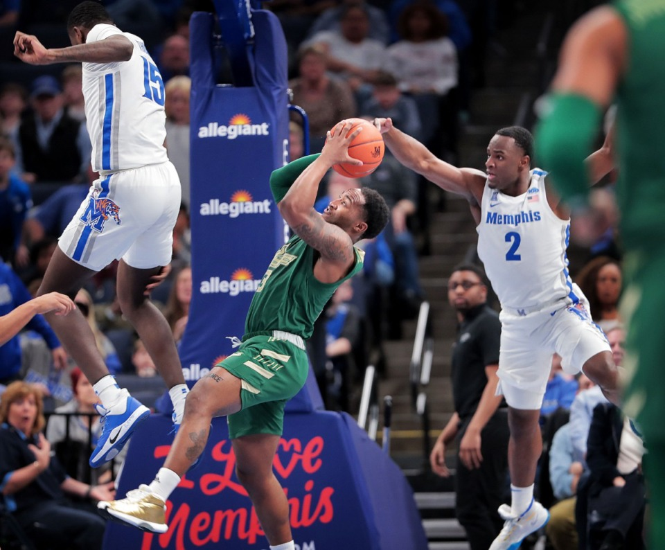 <strong>Guard Laquincy Rideau shoots under pressure by University of Memphis guard Alex Lomax (2) and Lance Thomas (15) during the Tigers' game on Feb. 8, 2020, against USF at the FedExForum in Memphis, TN.</strong> (Jim Weber/Daily Memphian)