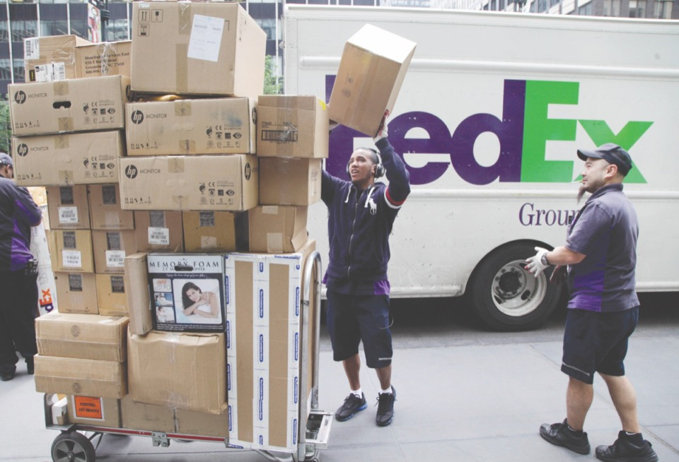<strong>In this Friday, May 11, 2012 file photo, FedEx workers sort boxes for delivery as they are unloaded from a FedEx truck in New York</strong>. (AP Photo/Mark Lennihan)