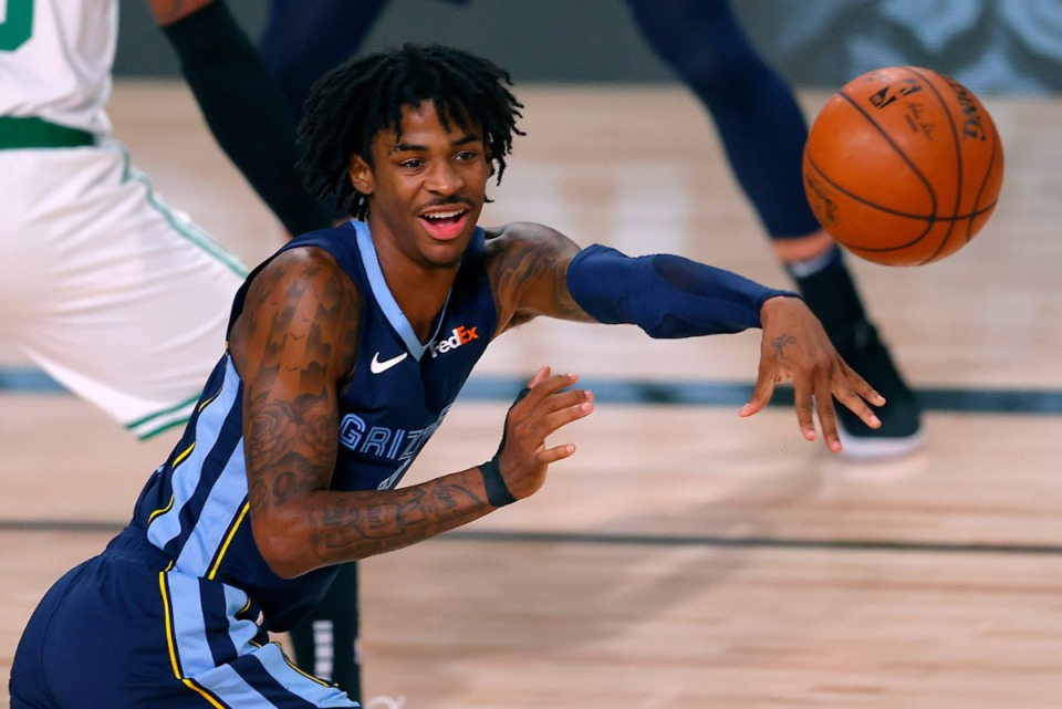 <strong>Memphis Grizzlies' Ja Morant passes the ball with his trademark grin on Aug. 11 during the second half of an NBA in Lake Buena Vista, Fla.</strong> (Mike Ehrmann, Pool, AP file)