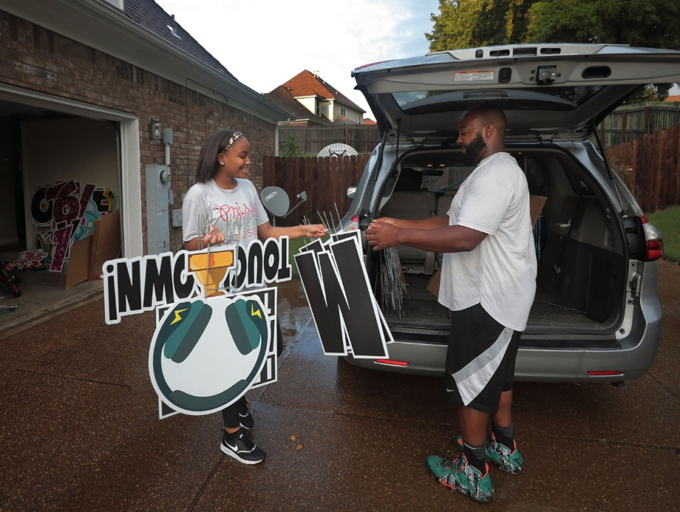 <strong>Jasmyn Lyons helps Steven Davis load the family car Aug. 28, 2020 for a yard sign business the family started. Each night Thursday through Sunday, they visit an average of 6 yards and set up signs for parties, anniversaries and other special events.</strong> (Patrick Lantrip/Daily Memphian)