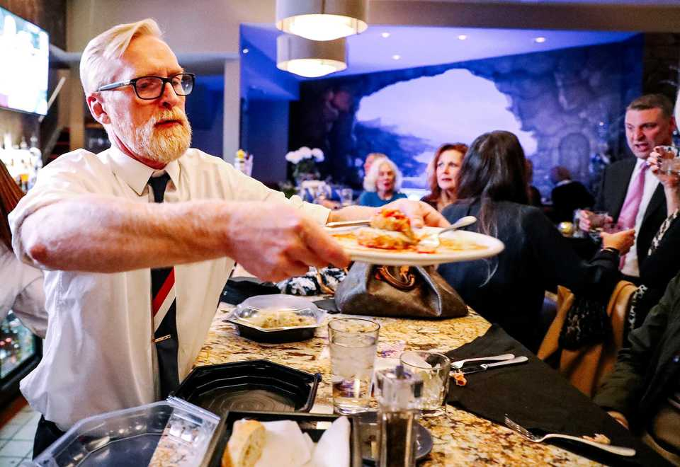 <strong>Ronnie Grisanti's bartender Chris Backey picks up finished entrees from guests at the L-shaped bar, which stays busy with a diverse crowd out for a quick drink or a long night.</strong> (Houston Cofield/Daily Memphian)