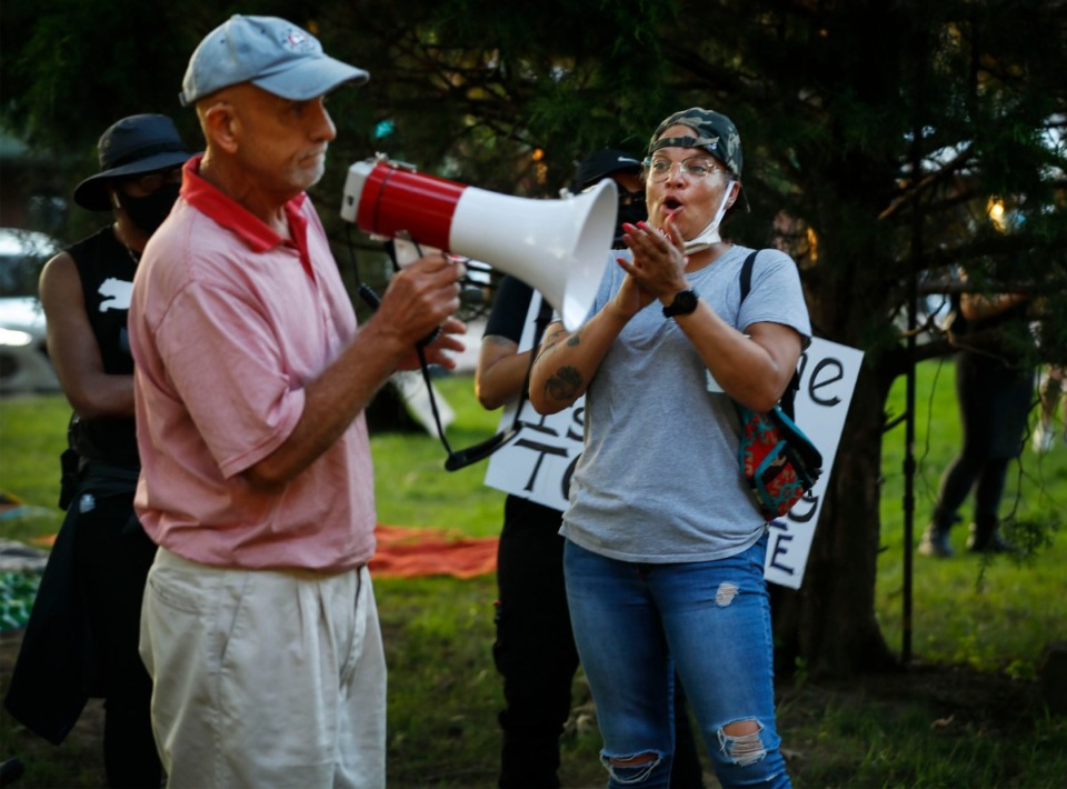 <strong>Activist LJ Abraham (right) claps as a bystander asks that a crowd gathered leave, as protesters hold a sit-in at Town Square Park on Monday, Sept. 7, 2020 in Collierville. A monument given to the town of Collierville by the United Daughters of Confederacy which sits in the park spurred a demonstration.</strong> (Mark Weber/The Daily Memphian)
