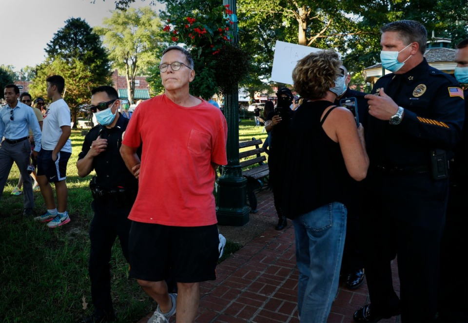 <strong>Collierville Police lead an unidentified man away in handcuffs after he knocked a cell phone out of the hands of Frances Marable (second right) during a sit-in at Town Square Park on Monday, Sept. 7, 2020. A monument given to the town of Collierville by the United Daughters of Confederacy spurred a demonstration.</strong> (Mark Weber/The Daily Memphian)