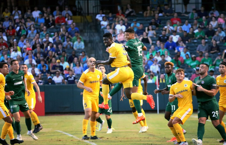 <strong>Memphis 901 FC defender Jacob Hauser-Ramsey (15) jumps for the ball while fighting off a Nashville defender during a July 2019 match.&nbsp;Hauser-Ramsey has re-signed with the team for the remainder of the 2020 season.</strong> (Patrick Lantrip/Daily Memphian file)