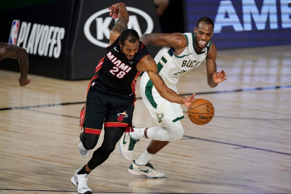 <strong>Miami Heat's Andre Iguodala (28) reaches for the ball in front of Milwaukee Bucks' Khris Middleton (22) on Sept. 8, 2020, in Lake Buena Vista, Fla. The Heat dispatched the Bucks in five games.</strong> (Mark J. Terrill/AP file)