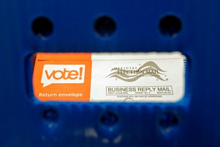 <strong>A vote-by-mail ballot is visible through the handle of a sorting tray.</strong> (Ted S. Warren/AP)
