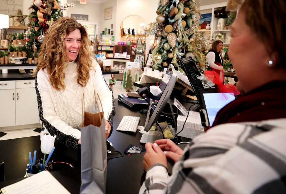 <strong>Tara Gorman (left), co-owner of The Truffle Pig, helps customer Debbie Alexander (right) with the purchase of a holiday ornament for a friend. </strong>(Houston Cofield/Daily Memphian)