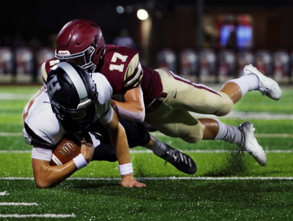 <strong>Houston High School quarterback Gray Nischwitz (5) gets dragged down by Evangelical Christian School safety Zachary Baker (17) during the game at Evangelical Christian School Sept. 11.</strong> (Patrick Lantrip/Daily Memphian)