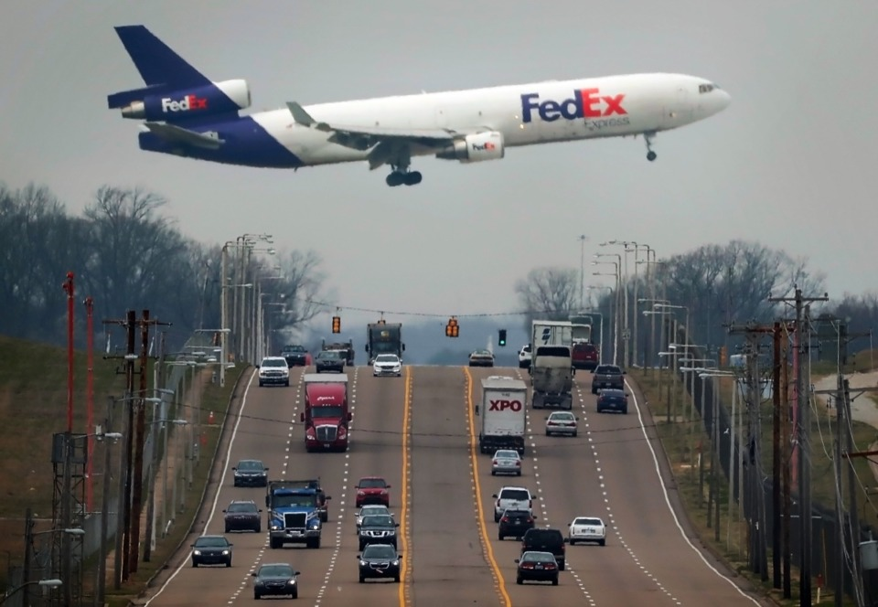 <strong>A FedEx plane passes low over Shelby Drive as it lands at Memphis International Airport.</strong> (Jim Weber/Daily Memphian)