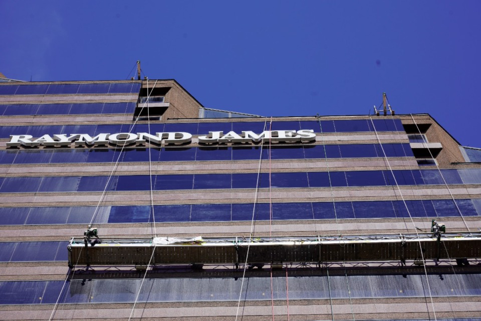 <strong>A crew works on the exterior of Downtown&rsquo;s 21-story Raymond James Tower in this file photo. Raymond James announced Sept. 15 it is laying off nearly 4% of its global workforce, including positions in Memphis.&nbsp;</strong>(Daily Memphian file)