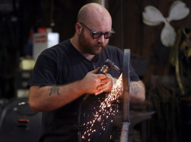 <strong>Reed Peck-Kriss files down an ornate metal handrail while inside the smithy at the Metal Museum Sept. 12, 2020.</strong> (Patrick Lantrip/Daily Memphian)