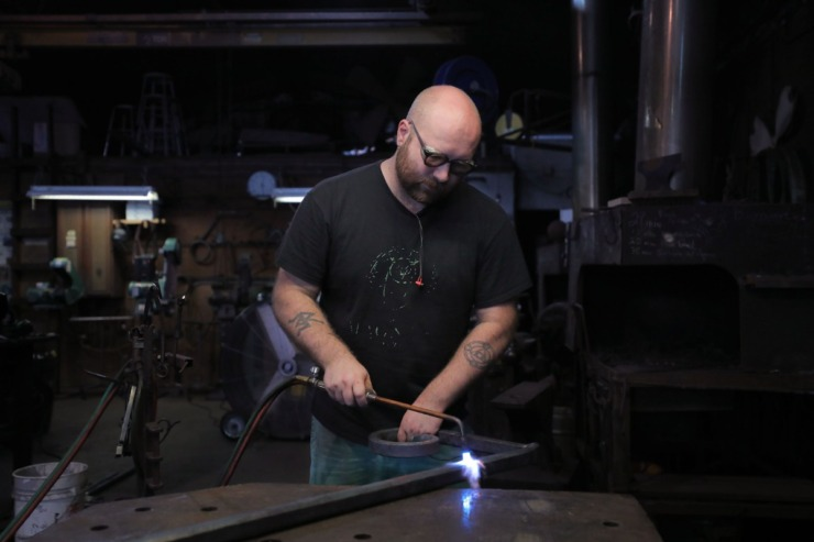 <strong>Blacksmith Reed Peck-Kriss works on an ornate metal handrail while inside the smithy at the Metal Museum Sept. 12, 2020.</strong> (Patrick Lantrip/Daily Memphian)