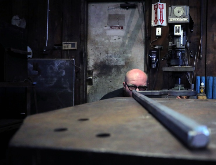 <strong>Blacksmith Reed Peck-Kriss makes sure a piece of metal is perfectly straight while inside the smithy at the Metal Museum Sept. 12, 2020.</strong> (Patrick Lantrip/Daily Memphian)