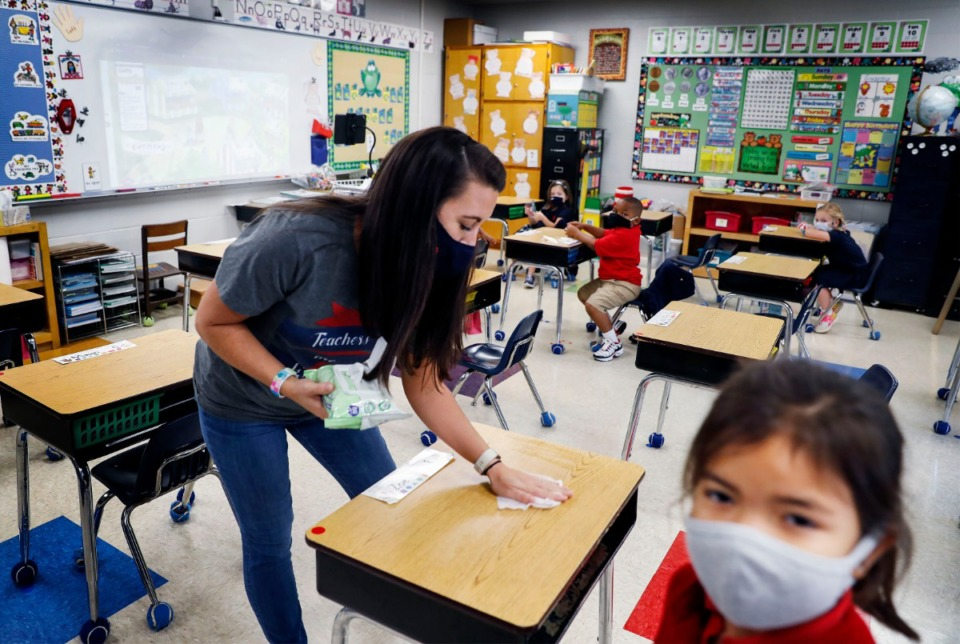 <strong>Harding Academy Lower School kindergarten teacher Mallory Gatlin uses a sanitized wipe to clean desks during a break in class on Friday Sept. 18, 2020.</strong> (Mark Weber/Daily Memphian)