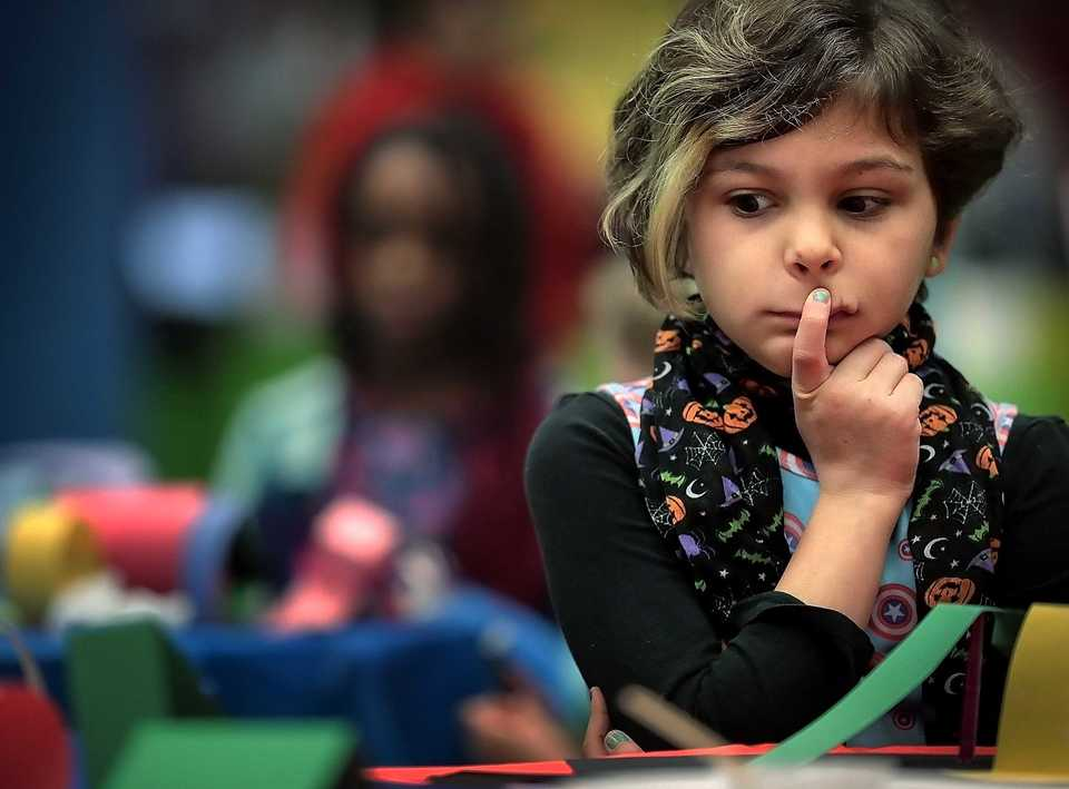 "<strong>Piper Williams, 9, ponders her next move while working on a 3D collage inspired by the children's book ""Over Under and Through"" during a family workshop at the Benjamin Hooks Library hosted on Dec. 15, 2018 by Studio Institute a NYC-based nonprofit which has placed artists in public school classrooms since the 70s. The Studio Institute is establishing a new program placing local artists in Shelby County preschools.</strong> (Jim Weber/Daily Memphian)"