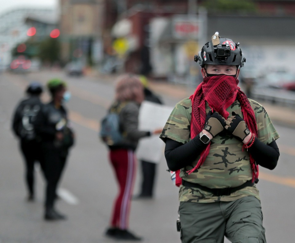 <strong>A protest marshal keeps an eye on the crowd while demonstrators block Poplar Avenue Downtown on Sept. 24.</strong> (Patrick Lantrip/Daily Memphian)