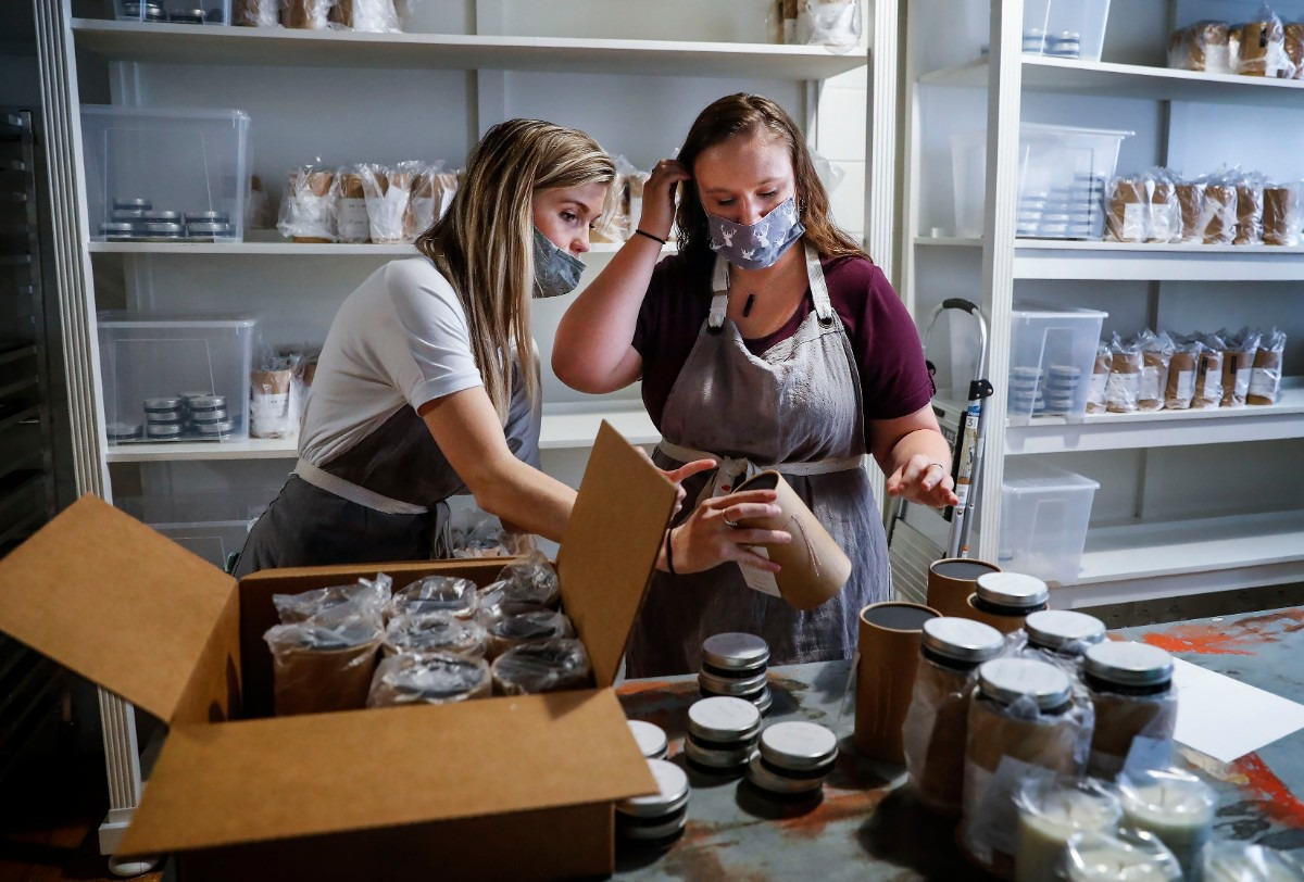 <strong>Re + New + All founder Lee Howard (left) and Kelsea Vaughn package candles for shipping on Sept. 15, 2020. The candle company offers employment and a brighter future for survivors of sex trafficking.</strong> (Mark Weber/The Daily Memphian)