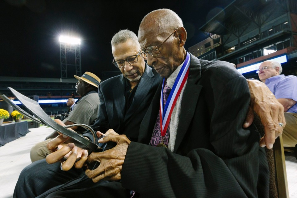 <strong>Jerry C. Johnson, right, looks at his Memphis Sports Hall of Fame award with his son, Dr. Jerry Johnson, at his induction on Oct. 10, 2019.</strong> (Ziggy Mack/Daily Memphian file)