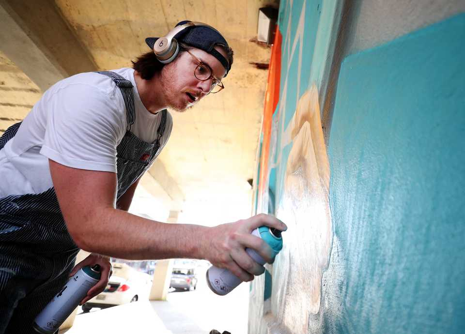 <strong>Artist and designer Kyle Taylor puts the finishing touches on a music mural near G.E. Patterson and S. Main Street. Taylor is Memphis artist who runs a new artist studio and collective, Rowdy Dept., that is housed behind Stock and Belle on S. Main Street.</strong> (Houston Cofield/Daily Memphian)
