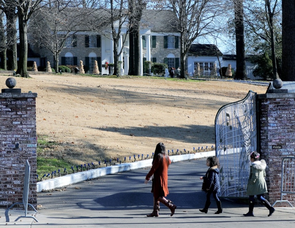 <strong>A family walks past the gates of Graceland on Dec. 11, 2019. Elvis&rsquo; grandson has been buried there.</strong> (Patrick Lantrip/Daily Memphian)