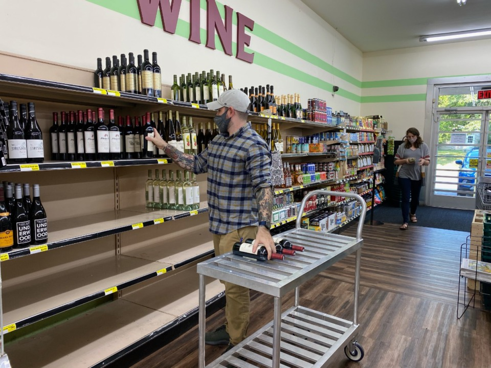 <strong>Taylor James stocks the shelves at High Point Grocery, which started selling wine on Wednesday.</strong> (Submitted)