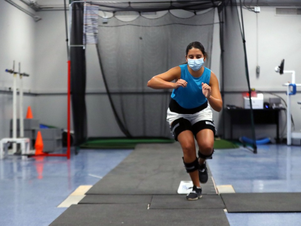 <strong>Daily Memphian reporter Danielle Lerner participates in a movement screening,&nbsp; which includes one-footed hops over a small obstacle, at the University of Memphis Human Performance Center.</strong> (Patrick Lantrip/Daily Memphian)