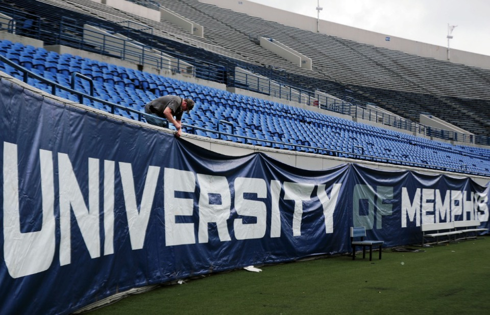 <strong>Curtis Smith hangs a University of Memphis banner at the Liberty Bowl Sept. 3, 2020 in anticipation the Tigers' home opener.</strong> (Patrick Lantrip/Daily Memphian)