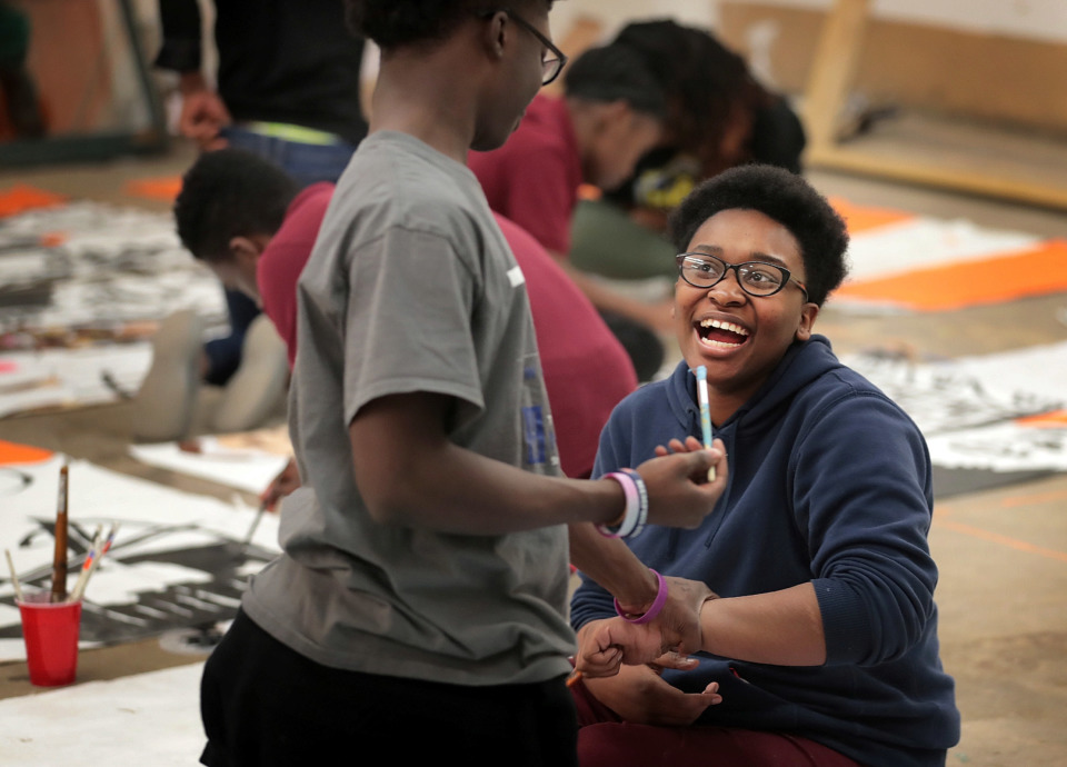 <strong>Kyra Macklin (right) tries to paint Devon Davis instead of the mural while joking around during an afterschool program on Dec. 18, 2018, for Melrose High School students at The Collective on Lamar Avenue.</strong> (Jim Weber/Daily Memphian)