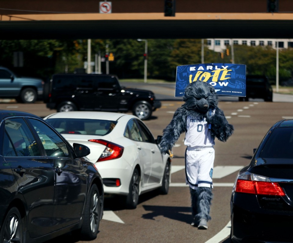 <strong>Grizz, the Memphis Grizzlies mascot hands out masks while encouraging people along Poplar Avenue to early vote Oct. 14, 2020.</strong> (Patrick Lantrip/Daily Memphian)