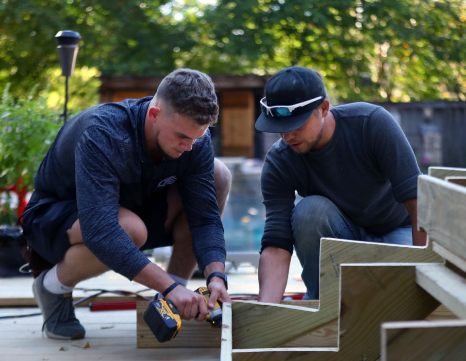 <strong>Aleksander Haight (right) shows Joey Magnifico the ropes while building a deck in the backyard of a Midtown home on Oct. 14, 2020.</strong> (Patrick Lantrip/Daily Memphian)