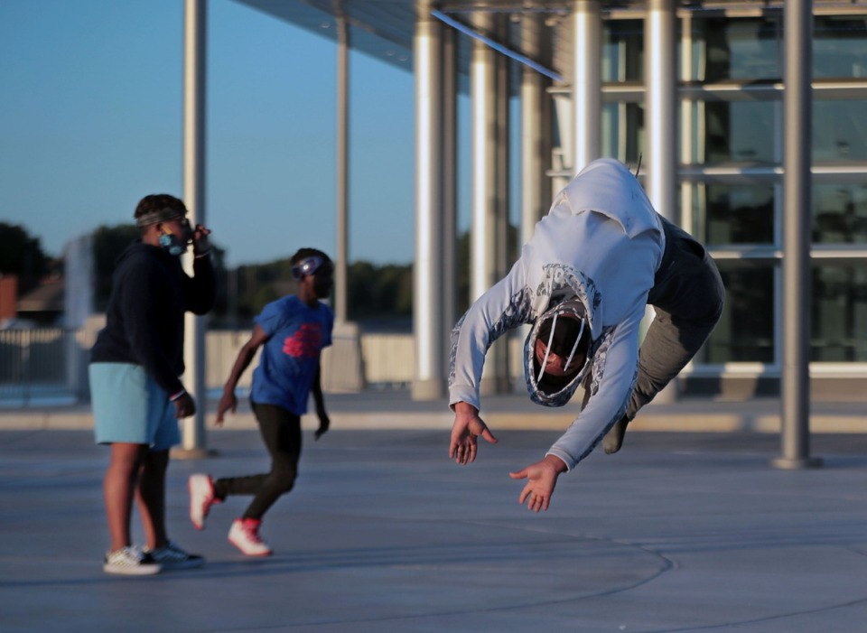 <strong>Tyjier Terrell with the Innovation Dance Company of Memphis does a flip while practicing a routine with Braylin Given (left) and Donovan Smith in the main plaza of the Raleigh Springs Civic Center on Friday, Oct. 16, 2020.</strong> (Patrick Lantrip/Daily Memphian)