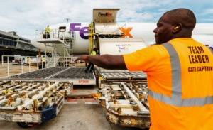 <strong>Anthony Givance directs a tug loaded with cargo to be shipped out on a FedEx freight jet at the Memphis hub in this file photo. FedEx will hold a job fair Saturday, Oct. 24, as it prepares for a record holiday shipping season.</strong> (Daily Memphian file)