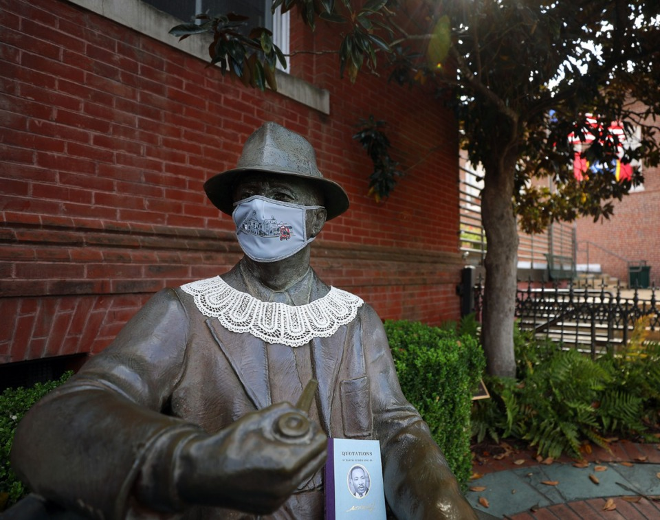<strong>A masked-statue of William Faulkner sits socially distanced on a bench in Oxford, Mississippi, with a Martin Luther King book in his lap.</strong> (Patrick Lantrip/Daily Memphian)